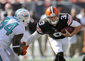 Photo - Cleveland Browns quarterback Brandon Weeden (3) is sacked by Miami Dolphins defensive tackle Randy Starks (94) in the fourth quarter of an NFL football game Sunday, Sept. 8, 2013, in Cleveland. Weeden was sacked five time in the Browns' 23-10 loss to Miami. (AP Photo/David Richard)