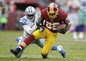 Photo - Washington Redskins wide receiver Pierre Garcon is hauled to the turf by Dallas Cowboys cornerback Brandon Carr during the second half of an NFL football game in Landover, Md., Sunday, Dec. 22, 2013. (AP Photo/Evan Vucci)