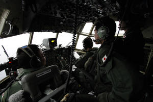 Photo - Japanese Air Self-Defense Force's Capt. Junichi Tanoue, left, co-pilot Ryutaro Hamahira, second from left, and engineer Noriyuki Yamanouchi, second from right, scan the ocean aboard a C130 aircraft while it flies over the southern search area in the southeastern Indian Ocean, 200 to 300 kilometers (124 to 186 miles) south of Sumatra, Indonesia, Friday, March 21, 2014. Search planes scoured a remote patch of the Indian Ocean but came back empty-handed Friday after looking for any sign of the missing Malaysia Airlines jet, another disappointing day in one of the world's biggest aviation mysteries. (AP Photo/Koji Ueda)