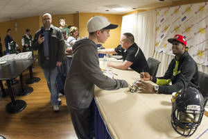 Photo - New York Jets quarterback Geno Smith, right, greets fans and signed autographs at the Charleston Civic Center Saturday, March 22, 2014 in Charleston, WV. (AP Photo/Michael Switzer)
