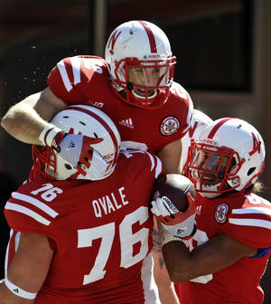 Photo -   Nebraska's Rex Burkhead, top, celebrates after scoring a touchown with teammates Brent Qvale (76) and Kenny Bell, right, during the first half of an NCAA college football game against Idaho State in Lincoln, Neb., Saturday, Sept. 22, 2012. (AP Photo/Dave Weaver)