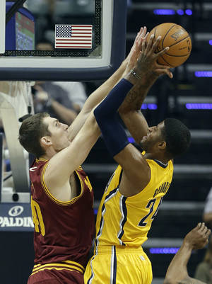 Photo - Indiana Pacers' Paul George, right, puts up a shot against Cleveland Cavaliers' Tyler Zeller during the first half of an NBA basketball game Saturday, Nov. 2, 2013, in Indianapolis. (AP Photo/Darron Cummings)
