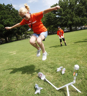 Photo -  Chrissa Gungoll, 12, jumps into the air to propel her plastic bottle rocket towards her grandfather Lanny Bainter during an aerospace class at Grandparent University, an annual event at Oklahoma State University in Stillwater. Grandparents stood at the other end of the lawn to track the height of the rocket. Photo by KT King/The Oklahoman  <strong>KT King -  The Oklahoman </strong>
