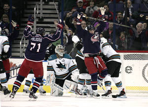 photo - Columbus Blue Jackets' Brandon Dubinsky (17) scores against San Jose Sharks goalie Thomas Greiss (1) during the first period of an NHL hockey game, Monday, Feb. 11, 2013, in Columbus, Ohio. Rushing in to celebrate is Blue Jackets' Nick Foligno. (AP Photo/Mike Munden)