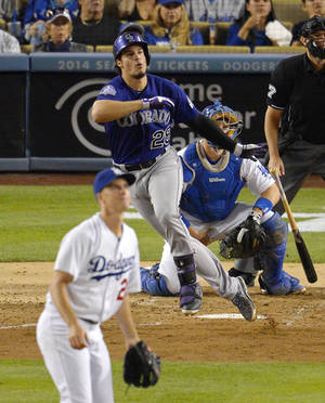 Photo - Colorado Rockies' Nolan Arenado, center, hits an RBI double as Los Angeles Dodgers starting pitcher Zack Greinke, left, and catcher A.J. Ellis look on during the fourth inning of their baseball game, Saturday, Sept. 28, 2013, in Los Angeles.  (AP Photo/Mark J. Terrill)