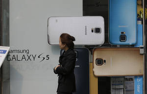 Photo - A woman walks by the advertisement of  Samsung's Galaxy S5 smartphone at a mobile phone shop in Seoul, South Korea, Thursday, March 27, 2014. The global launch of Samsung's latest smartphone is being upstaged by South Korean mobile network companies. SK Telecom, South Korea's largest mobile carrier, said it will start selling the Galaxy S5 on Thursday, two weeks before the scheduled sales launch on April 11. (AP Photo/Lee Jin-man)