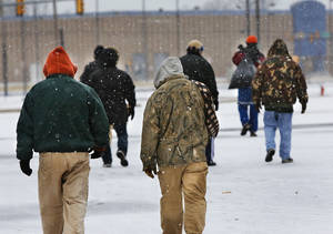 Photo - Men walk across a snow-covered lot Tuesday after leaving the Red Andrews Christmas Dinner in downtown Oklahoma City. Photo by  Jim Beckel,  The Oklahoman