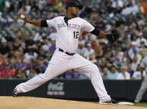 Photo - Colorado Rockies starting pitcher Juan Nicasio work against the Cincinnati Reds in the first inning of a baseball game in Denver on Saturday, Aug. 31, 2013. (AP Photo/David Zalubowski)