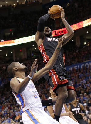Photo - Miami Heat forward LeBron James (6) is fouled by Oklahoma City Thunder forward Kevin Durant (35) during tthe first quarter of an NBA basketball game in Oklahoma City, Thursday, Feb. 20, 2014. (AP Photo/Sue Ogrocki)