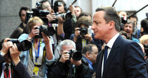 Photo - British Prime Minister David Cameron walks by the media as he arrives for an EU summit in Brussels on Thursday, March 20, 2014. The EU Commission president wants a two-day summit of European Union leaders to center on boosting the fledgling government in Kiev rather than focus exclusively on sanctions against Russia over its annexation of Ukraine's Crimea peninsula. (AP Photo/Eric Vidal)