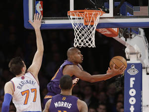 Photo - Phoenix Suns' Leandro Barbosa (10), of Brazil, drives past New York Knicks' Andrea Bargnani (77) during the first half of an NBA basketball game, Monday, Jan. 13, 2014, in New York. (AP Photo/Frank Franklin II)