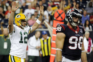 Photo -   Green Bay Packers quarterback Aaron Rodgers (12) celebrates a touchdown as Houston Texans outside linebacker Connor Barwin (98) walks away in the fourth quarter of an NFL football game, Sunday, Oct. 14, 2012, in Houston. The Packers won 42-24. (AP Photo/Dave Einsel)