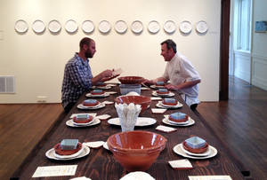 "Photo - This 2014 photo provided by the Philadelphia Art Alliance shows artist Gregg Moore, left, and chef  Pierre Calmels at a table set with Moore's fine ceramic pottery for a show called ""Heirloom,""  in Philadelphia. Calmels serves a seven-course, $150 dinner called ""Table d'Hote"" at the museum using Moore's pottery. Moore says the art, which is  part of a movement called social practice art, is created by the experience of the food, ceramics, museum space and the people sharing the meal.  (AP Photo/Philadelphia Art Alliance, Sarah Archer)"