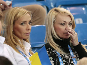 Photo - FILE - In this Saturday, Feb. 8, 2014 file photo, Yana Rudkovskaya, right, the wife of Russian figure skater Evgeni Plushenko, watches the team ice dance short dance figure skating competition with retired figure skater Tatiana Navka of Belarus at the Iceberg Skating Palace during the 2014 Winter Olympics in Sochi, Russia. In Russia, Plushenko is practically royalty, and being his wife has its benefits. (AP Photo/Ivan Sekretarev, File)