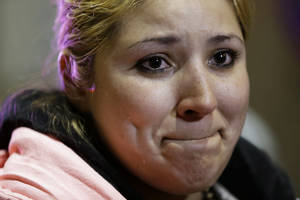 Photo - Maria Hernandez, of Angleton, Texas, a passenger from the disabled Carnival Triumph cruise ship, tears up as she describes the ordeal to reporters after arriving by bus at the Hilton Riverside Hotel in New Orleans, Friday, Feb. 15, 2013. The ship had been idled for nearly a week in the Gulf of Mexico following an engine room fire. (AP Photo/Gerald Herbert)