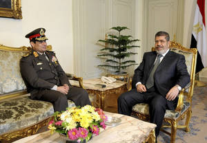 "Photo - FILE - In this Thursday Feb, 21, 2013 file photo, released by the Egyptian Presidency, Egyptian Minister of Defense, Lt. Gen. Abdel-Fattah el-Sissi, left, meets with Egyptian President Mohammed Morsi at the presidential headquarters in Cairo, Egypt. El-Sissi has warned that the military is ready to intervene to stop the nation from entering a ""dark tunnel"" of internal conflict. (AP Photo/Mohammed Abd El Moaty, Egyptian Presidency, File)"