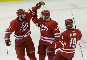 Photo - Carolina Hurricanes' Jay Harrison (44), Riley Nash (20) and Jiri Tlusty (19), of the Czech Republic, celebrate Nash's goal against the San Jose Sharks during the third period of an NHL hockey game in Raleigh, N.C., Friday, Dec. 6, 2013. Carolina won 5-3. (AP Photo/Gerry Broome)