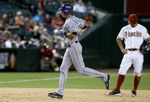 Photo - Colorado Rockies' Drew Stubbs, left, rounds the bases after hitting a home run as Arizona Diamondbacks' Eric Chavez, right, kicks the dirt during the ninth inning of a baseball game Tuesday, April 29, 2014, in Phoenix. The Rockies defeated the Diamondbacks 5-4. (AP Photo/Ross D. Franklin)
