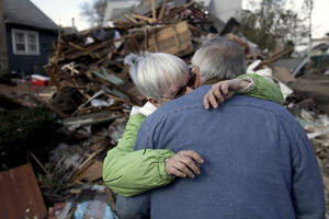 Photo - Sheila and Dominic Traina hug in front of their home which was demolished during Superstorm Sandy in Staten Island, N.Y., Friday, Nov. 2, 2012.  Mayor Michael Bloomberg has come under fire for pressing ahead with the New York City Marathon. Some New Yorkers say holding the 26.2-mile race would be insensitive and divert police and other important resources when many are still suffering from Superstorm Sandy. The course runs from the Verrazano-Narrows Bridge on hard-hit Staten Island to Central Park, sending runners through all five boroughs. The course will not be changed, since there was little damage along the route.  (AP Photo/Seth Wenig) ORG XMIT: NYSW106