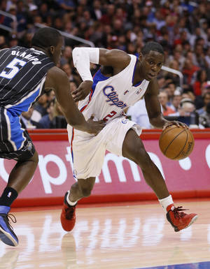 Photo - Los Angeles Clippers' Darren Collison, right, drives around Orlando Magic's Victor Oladipo, left, during the first half of an NBA basketball game in Los Angeles, Monday, Jan. 6, 2014. (AP Photo/Danny Moloshok)