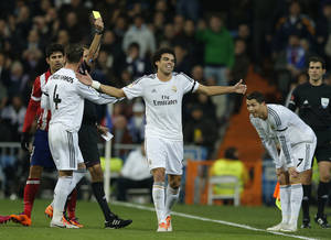 Photo - Real's Pepe, center, and Cristiano Ronaldo, right, laugh as Pepe gets a yellow card during the semifinal, 1st leg, Copa del Rey soccer derby match between Real Madrid and Atletico Madrid at the Santiago Bernabeu Stadium in Madrid, Wednesday Feb. 5, 2014. (AP Photo/Paul White)