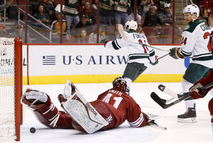 Photo - Minnesota Wild's Justin Fontaine (14) scores against Phoenix Coyotes' Mike Smith, left, as Wild's Matt Cooke (24) looks on during the first period in an NHL hockey game, Thursday, Jan. 9, 2014, in Glendale, Ariz. (AP Photo/Ross D. Franklin)