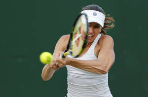 Photo - Martina Hingis of Switzerland, plays a return as she plays with partner Vera Zonareva of Russia against Carla Black of Zimbabwe and Sania Mizra of India during their match at the All England Lawn Tennis Championships in Wimbledon, London, Wednesday, June 25, 2014. (AP Photo/Ben Curtis)