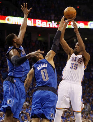 photo - Oklahoma City's Kevin Durant (35) takes the game-winning shot over Dallas' Shawn Marion (0) and Ian Mahinmi (28) during game one of the first round in the NBA playoffs between the Oklahoma City Thunder and the Dallas Mavericks at Chesapeake Energy Arena in Oklahoma City, Saturday, April 28, 2012. Oklahoma City won, 99-98. Photo by Nate Billings, The Oklahoman