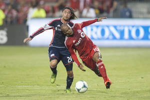 Photo - Toronto FC 's Robert Earnshaw , right,  tries to take the ball past New England Revolution's Lee Nguyen during first half of a MLS soccer game  in Toronto on Friday Aug.  30, 2013.  (AP Photo/The Canadian Press, Chris Young)