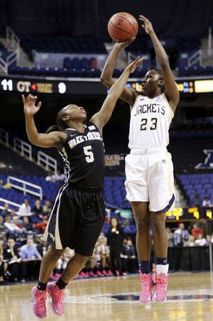 Photo - Georgia Tech's Sydney Wallace (23) shoots over Wake Forest's Chelsea Douglas (5) during the first half of an NCAA college basketball game at the Atlantic Coast Conference tournament in Greensboro, N.C., Thursday, March 7, 2013. (AP Photo/Chuck Burton)
