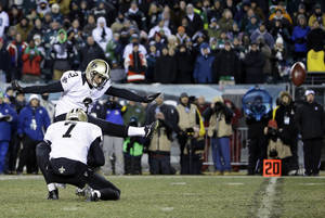 Photo - New Orleans Saints' Shayne Graham kicks the game-winning field goal in front of teammate Luke McCown during the second half of an NFL wild-card playoff football game against the Philadelphia Eagles, Saturday, Jan. 4, 2014, in Philadelphia. (AP Photo/Matt Rourke)