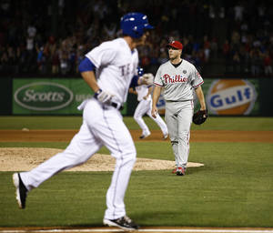 Photo - Philadelphia Phillies relief pitcher Jonathan Papelbon, right, leaves the field after walking in Texas Rangers' Jim Adduci, left, during the ninth inning of a baseball game on Wednesday, April 2, 2014, in Arlington, Texas. The Rangers won 4-3. (AP Photo/Jim Cowsert)