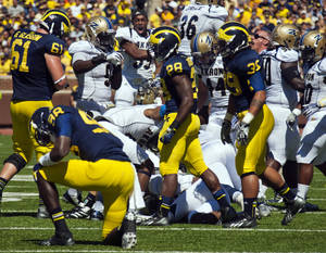 Photo - Michigan quarterback Devin Gardner (98) kneels on the field after fumbling the ball as Akron defenders celebrating the recovery in the second quarter of an NCAA college football game, Saturday, Sept. 14, 2013, in Ann Arbor, Mich. (AP Photo/Tony Ding)