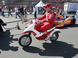 Photo - Driver Scott Dixon, of New Zealand, rides on a scooter in the pit road prior to a practice round for the MAVTV 500 IndyCar World Championship at Auto Club Speedway, Friday, Oct. 18, 2013 Fontana, Calif. (AP Photo/Alex Gallardo)