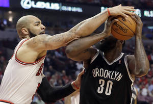 Photo - Chicago Bulls forward Carlos Boozer, left, defends against Brooklyn Nets forward Reggie Evans during the first half in Game 6 of their first-round NBA basketball playoff series in Chicago, Thursday, May 2, 2013. (AP Photo/Nam Y. Huh)