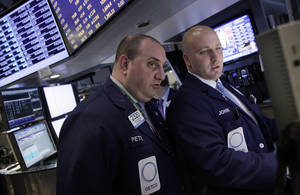 Photo -   Specialists Peter Giacchi, left, and John Parisi confer on the floor of the New York Stock Exchange Wednesday, April 25, 2012. U.S. stocks were headed for a neutral opening, with Dow Jones industrial futures nearly unchanged. (AP Photo/Richard Drew)
