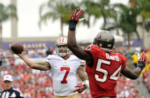 Photo - San Francisco 49ers quarterback Colin Kaepernick (7) gets away from Tampa Bay Buccaneers outside linebacker Lavonte David (54) as he throws a touchdown pass to wide receiver Michael Crabtree during the first quarter of an NFL football game, Sunday, Dec. 15, 2013, in Tampa, Fla. (AP Photo/Brian Blanco)