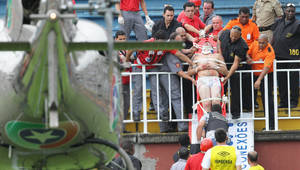 Photo - File - In this Dec. 8, 2013 file photo, an injured fan is carried on a stretcher after clashes with team fans during a Brazilian league soccer match between Atletico Paranaense and Vasco da Gama in Joinville, southern Brazil. Brazilians fans idolize their stars on the fields, courts and tracks. They'll cheer loudly at any sporting event they'll go to, be it a World Cup match, a Formula One race or a mixed martial arts fight. (AP Photo/Agencia O Dia, Carlos Moraes, File)
