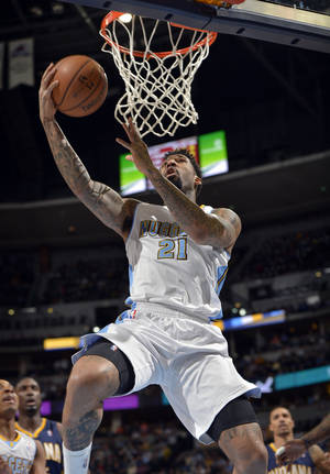 Photo - Denver Nuggets small forward Wilson Chandler (21) goes up for a shot against the Indiana Pacers during the first quarter of an NBA basketball game Saturday, Jan. 25, 2014, in Denver. (AP Photo/Jack Dempsey)