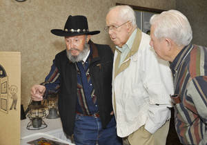 Photo - Tom Birkle, left, Wes Schuler and Sonny Hines check out an exhibit March 3 during a reunion for railroad employees in Oklahoma City. Photo by M. Tim Blake,  for The Oklahoman