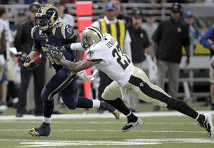 Photo - St. Louis Rams running back Zac Stacy, left, slips past New Orleans Saints safety Malcolm Jenkins on his way to a 40-yard touchdown run during the second quarter of an NFL football game Sunday, Dec. 15, 2013, in St. Louis. (AP Photo/Tom Gannam)