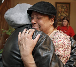 photo - Lisa Williamson, mother of Brandon A. Murray, hugs her son's friend Monday, March 11, 2013, in Warren, Ohio. Investigators spent Monday trying to piece together why eight teenagers were crammed into a speeding SUV without the owner's permission when it flipped over into a pond, killing six of them, including Murray. (AP Photo/Tony Dejak)