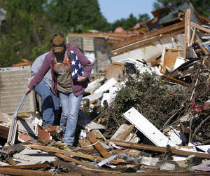 Photo - Ashley Hort carries her late grandfather's flag out after a tornado struck Woodward, Okla., Sunday, April 15, 2012. Photo by Bryan Terry, The Oklahoman