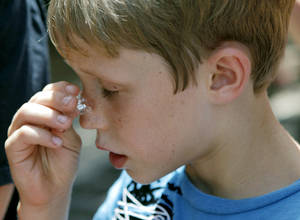 Photo - FILE - Jayden Disiere, 8, of Abilene, Texas, presses an ice cube to his nose as he cools off during a visit to the Oklahoma City Zoo in Oklahoma City on Thursday, July 21, 2011. Photo by John Clanton,