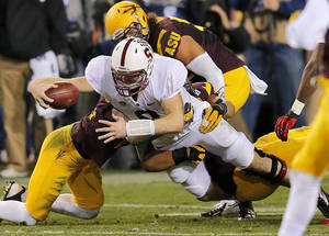 Photo - Stanford quarterback Kevin Hogan dives for a first down as he his pulled down by Arizona State defenders during the first half of the  NCAA Pac-12 Championship football game, Saturday, Dec. 7, 2013, in Tempe, Ariz. (AP Photo/Matt York)