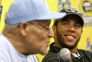 Photo - Darrell Wallace Jr., right, winner of Saturday's NASCAR Camping World Truck race, smiles as he listens to Wendell Scott Jr., left, during a news conference at Martinsville Speedway in Martinsville, Va., Sunday, Oct. 27, 2013. (AP Photo/Steve Helber)