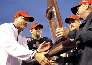 photo - Arkansas State head coach Gus Malzahn, from left, quarterback Ryan Aplin and linebacker Nathan Herrold are presented with the Sun Belt Conference trophy following their NCAA college football game against Middle Tennessee on Saturday, Dec. 1, 2012, in Jonesboro, Ark. (AP Photo/The Jonesboro Sun, Krystin McClellan)