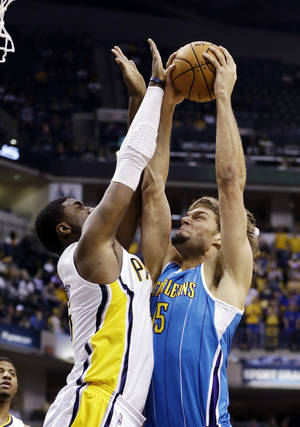 Photo -   New Orleans Hornets' Robin Lopez, right, has his shot blocked by Indiana Pacers' Roy Hibbert during the first half of an NBA basketball game, Wednesday, Nov. 21, 2012, in Indianapolis. (AP Photo/Darron Cummings)