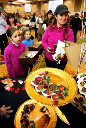 Photo - Ana Bolino and daughters Lindsay, left, and Mackenzie line up for chocolate-dipped strawberries at last year's Chocolate Festival sponsored by the Firehouse Art Center in Norman. OKLAHOMAN ARCHIVE photo
