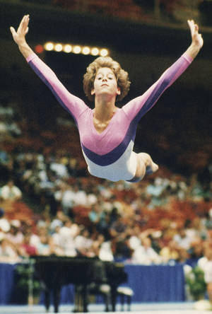 Photo - FILE - In this July 1988 file photo, U.S. gymnast Phoebe Mills flies through the air as she performs her floor exercise at the U.S. Gymnastics Championships in Houston, Texas. Mills used to flip for Olympic medals. These days, she decides who wins them. The 1988 U.S. gymnastics champion and Olympic bronze medalist is working in the snowboarding judging booth at the Sochi Games, giving marks in both the halfpipe and slopestyle contests at Rosa Khutor Extreme Park.  (AP Photo/David Breslauer, File)